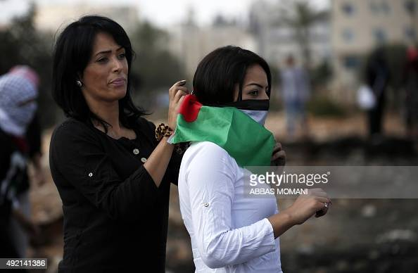 A Palestinian woman covers the face of a fellow protester with a national flag during clashes with Israeli security forces in Beit El Jewish...