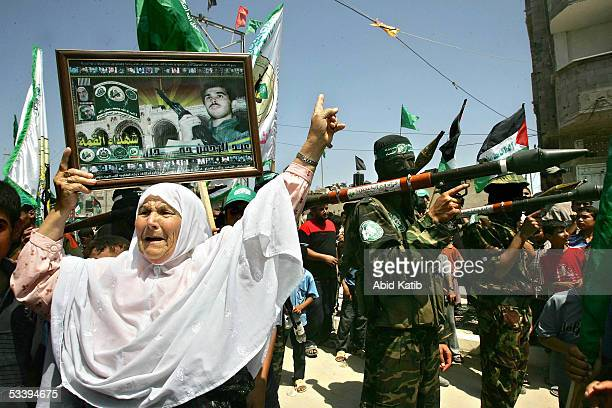 Palestinian woman dances in front of members of the Ezz AlDeen AlQassam military wing of the Islamic resistance movement Hamas as they march in front...