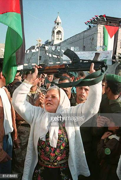Palestinian woman dances with a rifle in front of the Church of Nativity in Manger Square in Bethlehem 22 December The Palestinian Authority took...