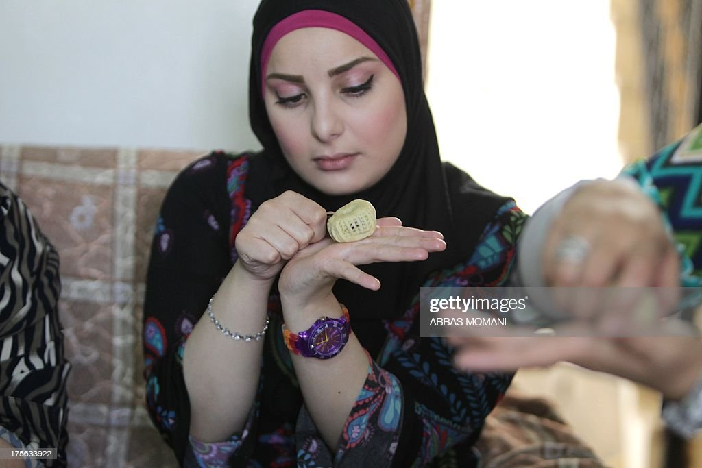 A Palestinian woman decorates traditional biscuits popular on the occasion of Eid al-Fitr at her home in the West Bank city of Ramallah, on August 5, 2013. Muslims around the world are preparing to celebrate the Eid al-Fitr holiday, which marks the end of the fasting month of Ramadan. Preparations include buying new clothes, toys and special sweets.
