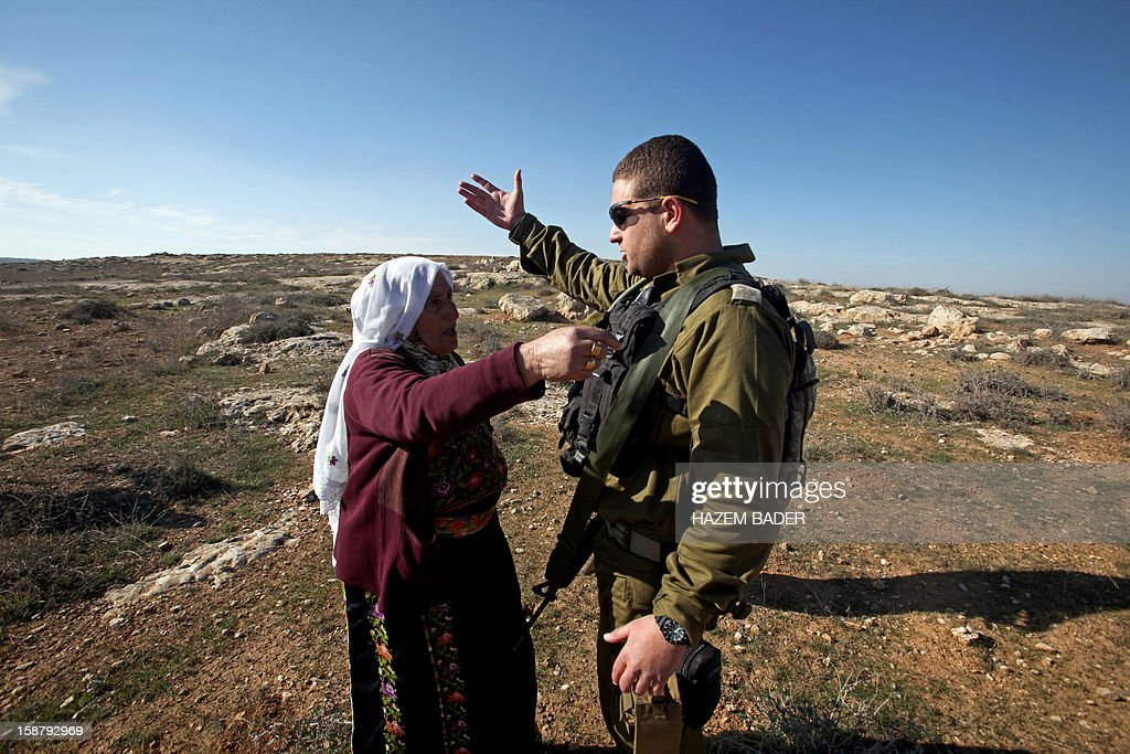 A Palestinian woman disputes with an Israeli soldier as they evacuate Palestinian land owners trying to farm on their land near the Jewish settlement of Sosia, in the village of Yatta south of the West Bank city of Hebron on December 29, 2012. Palestinian farmers are restricted from cultivating their land in the disputed area near the city of Hebron due to the Israeli settlements and military zone nearby. AFP PHOTO / HAZEM BADER