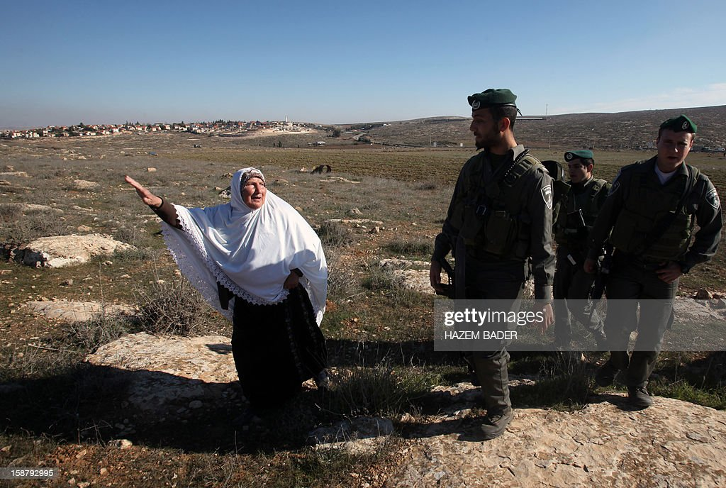 A Palestinian woman disputes with Israeli soldiers as they evacuate Palestinian land owners trying to farm on their land near the Jewish settlement of Sosia, in the village of Yatta south of the West Bank city of Hebron on December 29, 2012. Palestinian farmers are restricted from cultivating their land in the disputed area near the city of Hebron due to the Israeli settlements and military zone nearby. AFP PHOTO / HAZEM BADER
