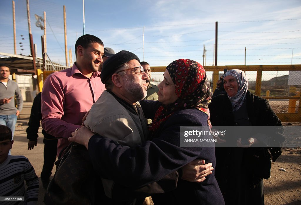 A Palestinian woman embraces Sheikh Hassan Yousef (L), a prominent leader of the Hamas Islamic movement, following his release on January 19, 2014 after spending 28 months in Israel's Ofer prison, near the West Bank city of Ramallah. Yousef, who is also a member of the Ramallah-based Palestinian Legislative Council, told reporters after being released that he would work with Hamas rivals 'Fatah and other Palestinian factions to achieve reconciliation.'