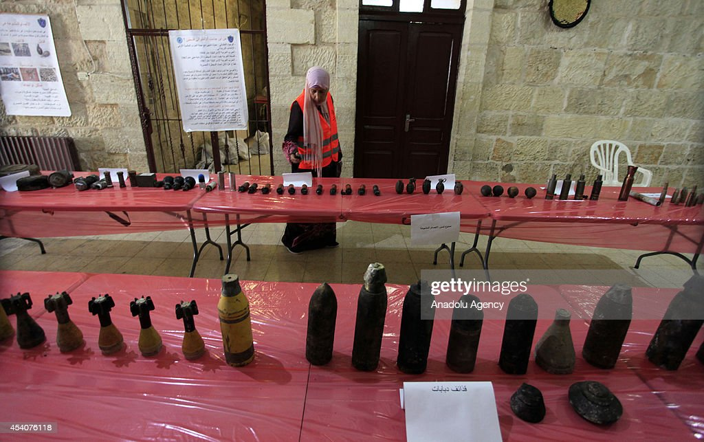 A Palestinian woman examines ammunitions, that Israel army use on the attacks on Gaza, at an exhibition in Ramallah, West Bank on 24 August, 2014. Gas bomb, hand grenade, plastic bullet, real bullet, rocket and other ammunitions of Israel army are displayed at the exhibition.