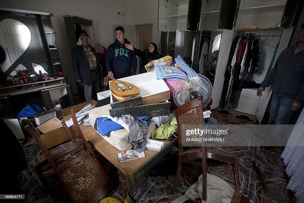 A Palestinian woman from the Siyam family, looks at a ransacked room after Israeli soldiers entered her house in East Jerusalem's Arab neighbourhood of Silwan, on February 6, 2013, during a neighborhood search operation for the past few days, in which several Palestinians have been arrested.