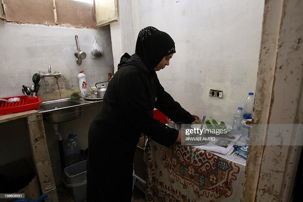 Palestinian woman from the Syrian refugee camp of Yarmuk works in the kitchen of her temporary home at the Shatila refugee camp in the Lebanese capital Beirut on December 19, 2012. Some 13,000 members of Syria's Palestinian refugee community have gone back to square one in neighbouring Lebanon. Like their ancestors, they too have been forced to flee their birthplace into exile.
