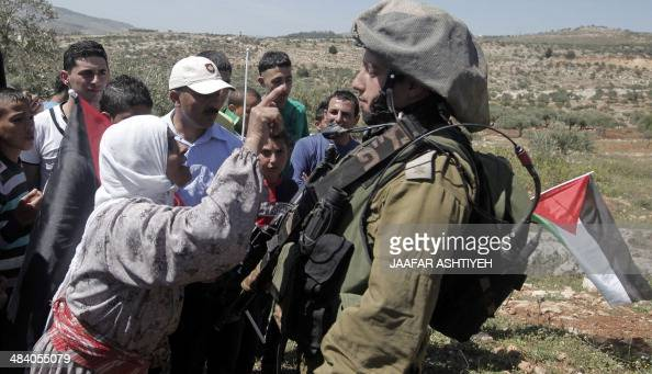 A Palestinian woman gestures talking to an Israeli soldier during a weekly protest against the confiscation of land by Israel on April 11 2014 in the...