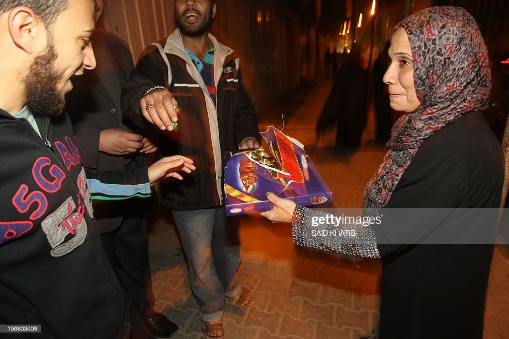 A Palestinian woman gives out sweets as people celebrate the beginning of the truce with Israel in Rafah town in the southern Gaza Strip on November 21, 2012. Palestinians in Gaza took to the streets to celebrate the start of a truce deal with Israel that was announced in Egypt on the eighth day of violence in and around Gaza.