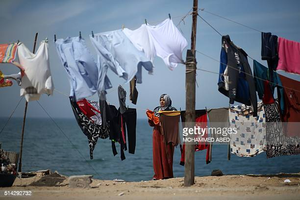 Palestinian woman hangs her laundry next to her house at alShatee refugee camp in Gaza City on March 8 2016 / AFP / MOHAMMED ABED