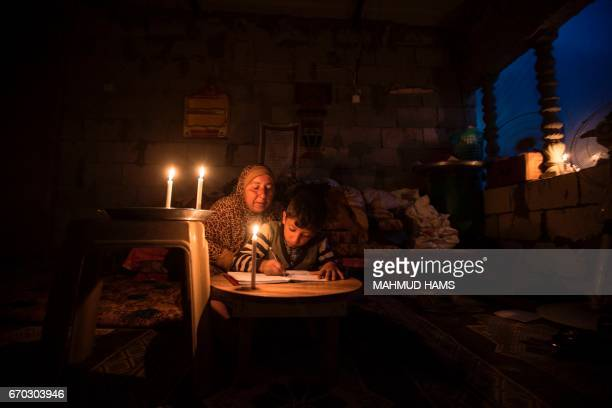 A Palestinian woman helps her son study by candlelight at their makeshift home in the Khan Yunis refugee camp in the southern Gaza Strip on April 19...
