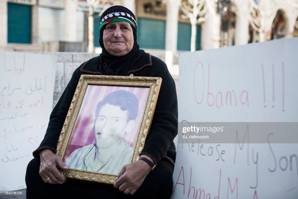 A Palestinian woman holding a photograph sits in protest outside the church of nativity before the official visit of U.S. President Barack Obama on March 22, 2013 in Bethlehem, West Bank. This is Obama's first visit as president to the region and his itinerary includes meetings with the Palestinian and Israeli leaders as well as a visit to the Church of the Nativity in Bethlehem.