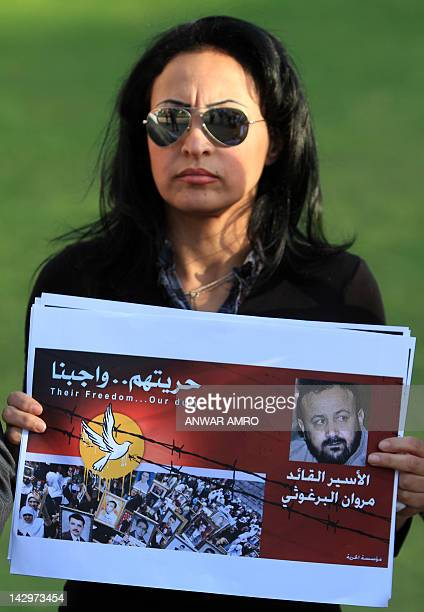 A Palestinian woman holding a picture of jailed Fatah leader Marwan Barghuti protests outside the United Nations Headquarters in Beirut on the eve of...