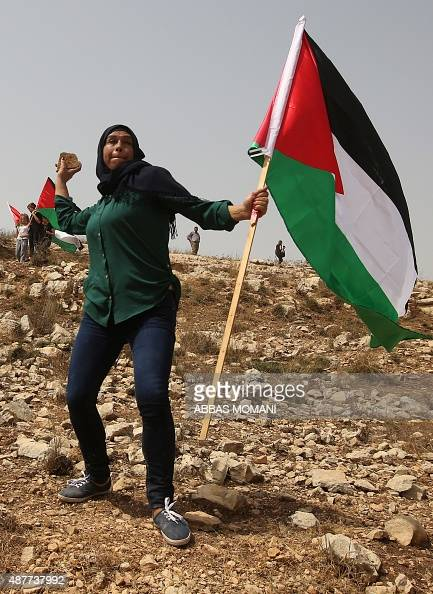 A Palestinian woman holding her national flag throws stones at Israeli troops during clashes during a demonstration against Jewish settlements in the...