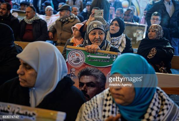 Palestinian woman holds a banner during a a demonstration in support of her relatives held in Israeli prisons in front of the International Red Cross...