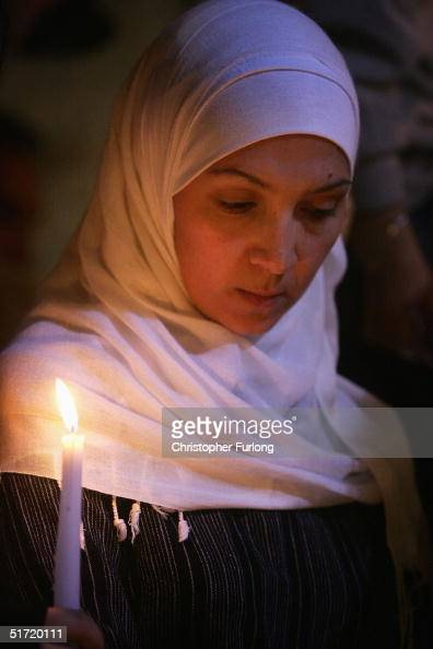 Palestinian woman holds a candlelight vigil outside President Yasser Arafat's Muqataa headquarters November 10 2004 in Ramallah in the West Bank In...