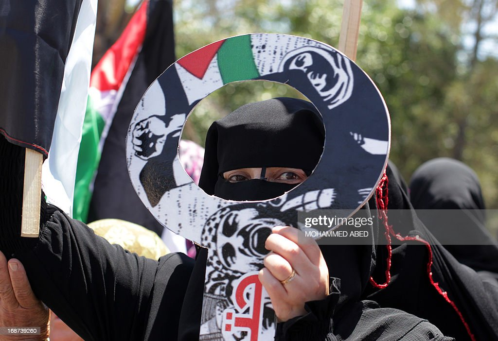 A Palestinian woman holds a cardboard cut-out of a key during a Nakba (catastrophe) rally in Gaza City, on May 14, 2013. Palestinians mark Nakba, or catastrophe in Arabic, which commemorates the exodus of hundreds of thousands of Palestinians after the establishment of Israel state in 1948.