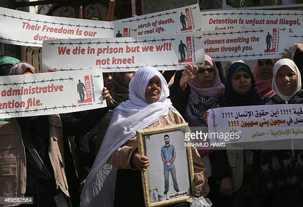 A Palestinian woman holds a framed portrait of her imprisoned son during a protest calling for the release of Palestinian prisoners held in Israeli...