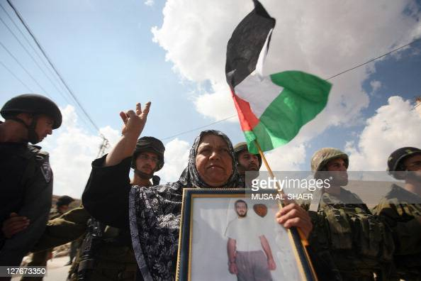A Palestinian woman holds a national flag and a picture of a detained relative as she stands in front of a cordon of Israeli troops during a...