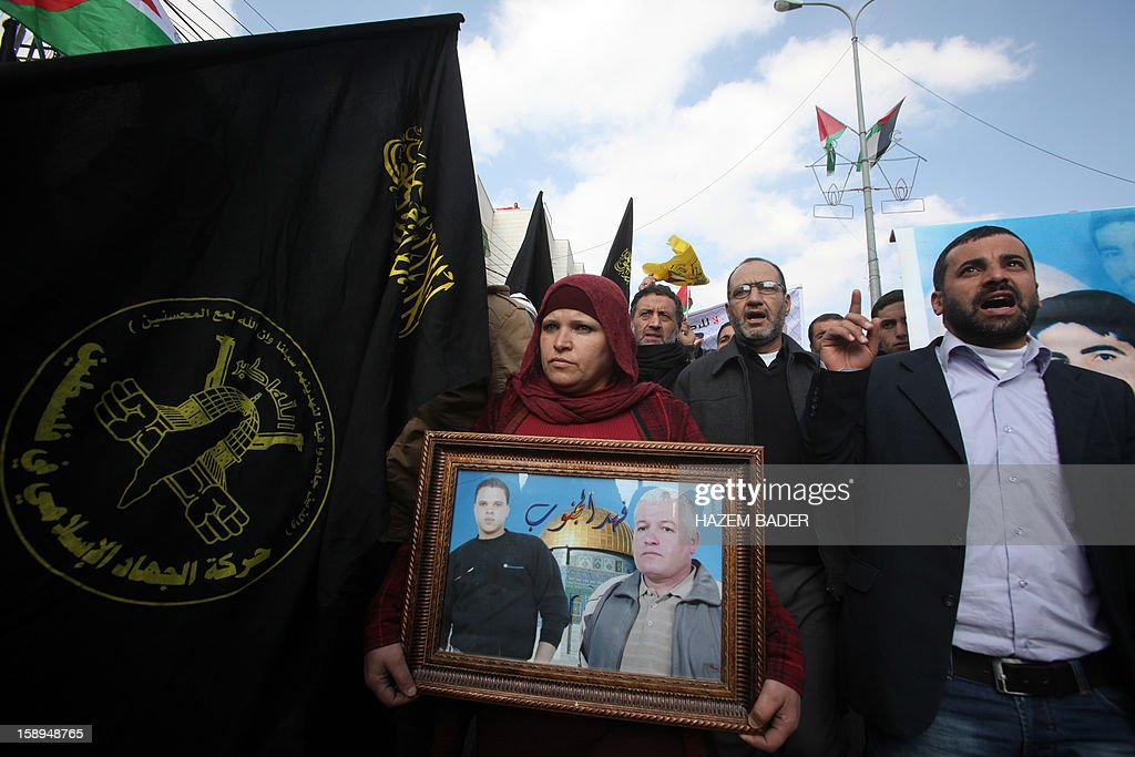 A Palestinian woman holds a picture featuring portraits of relatives being held in an Israeli prison as demonstrators hold up an Islamic Jihad movement flag and chant slogans during a protest in support with Palestinian prisoners on hunger strike against administrative detention in the West Bank city of Hebron on January 4, 2013. AFP PHOTO/HAZEM BADER