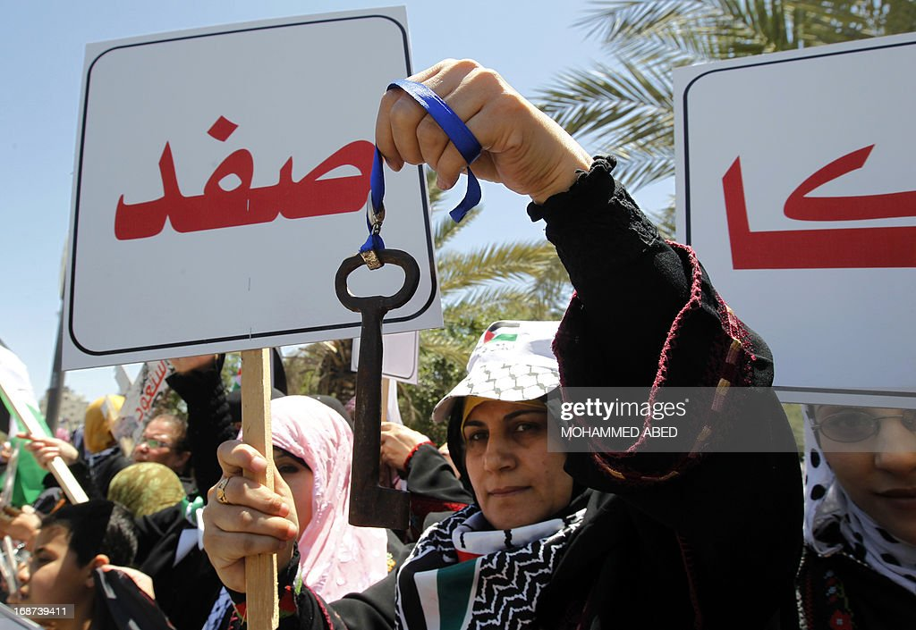 A Palestinian woman holds a placard written in Arabic 'Safed' (northern Israeli town) and a key during a rally in Gaza City, on May 14, 2013 as Palestinians start to mark Nakba, or catastrophe in Arabic, which commemorates the exodus of hundreds of thousands of Palestinians after the establishment of Israel state in 1948.