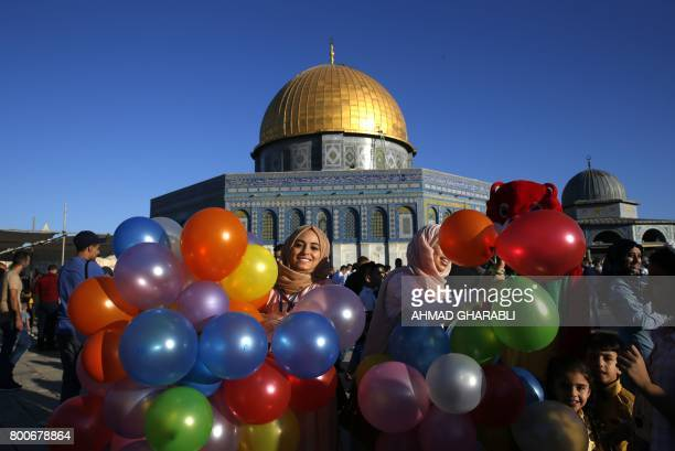 Palestinian woman holds balloons as Muslims gather for the morning Eid alFitr prayer near the Dome of Rock at the AlAqsa Mosque compound Islam's...