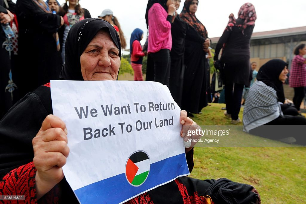 A Palestinian woman holds banners during a protest after the UNRWA decision to reduce the health, finance and education services, in front of the United Nations Relief and Works Agency for Palestine Refugees in the Near East (UNRWA) office in Beirut, Lebanon on May 6, 2016.