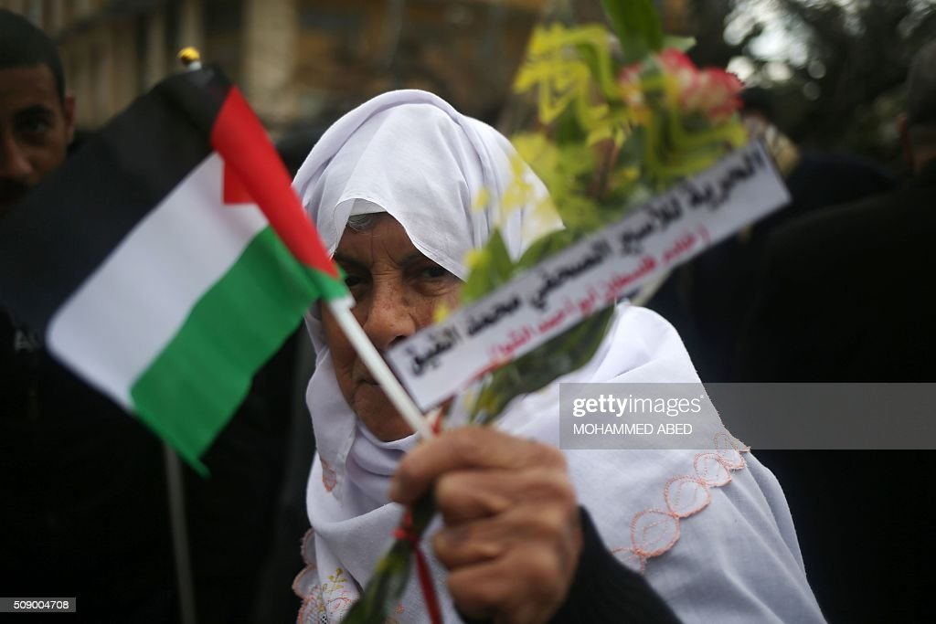 A Palestinian woman holds flowers and her national flag during a demonstration in support of hunger striking Palestinian journalist Mohammed al-Qiq, on February 8, 2016, in Gaza City. The 33-year-old television reporter will keep up his 10-week hunger strike despite Israel suspending a detention without trial order against him, his lawyer said. / AFP / MOHAMMED ABED