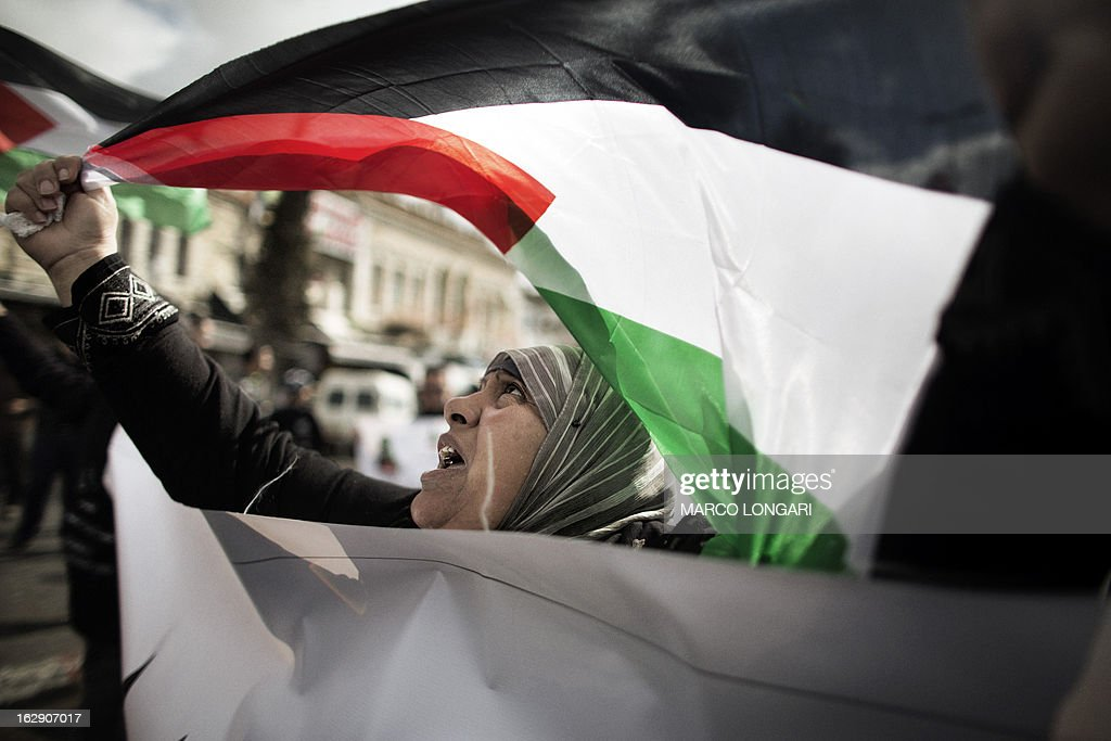 A Palestinian woman holds her national flag as she protests against Jerusalem's third annual marathon on March 1, 2013. About 20,000 runners took part in Jerusalem's third annual marathon, with 1,000 police deployed to provide security along the route, police said. The Palestine Liberation Organisation had called for a boycott of the marathon, part of which went through annexed east Jerusalem. AFP PHOTO/MARCO LONGARI