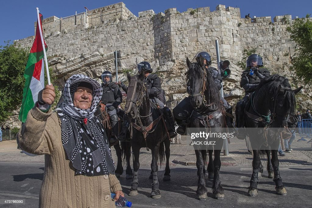 A Palestinian woman holds her national flag in front of Israeli policemen outside Damascus Gate in Jerusalem's old city on May 17 as she protests...