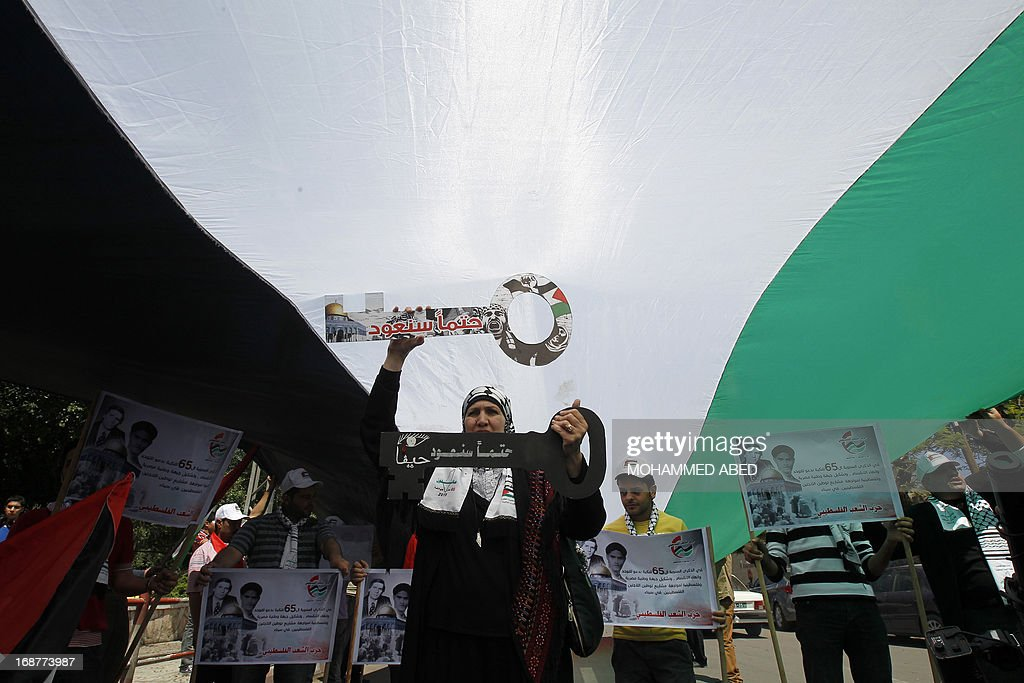 A Palestinian woman holds replicas of house keys, representing the front door keys of abandoned homes, as she attends a Nakba day or 'Day of Catastrophe' rally in Gaza City, on May 15, 2013. Palestinians and Arab Israelis are marking what to them is the Nakba -- Arabic for 'catastrophe' -- of the creation of the Jewish state and exodus of 760,000 of them from their homes in 1948.