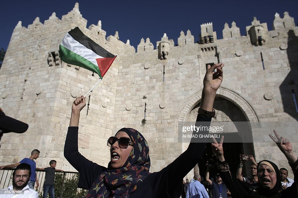 A Palestinian woman holds up a national flag as she demonstrates outside Damascus Gate in Jerusalem's old city on May 17 against the 'flag march'...