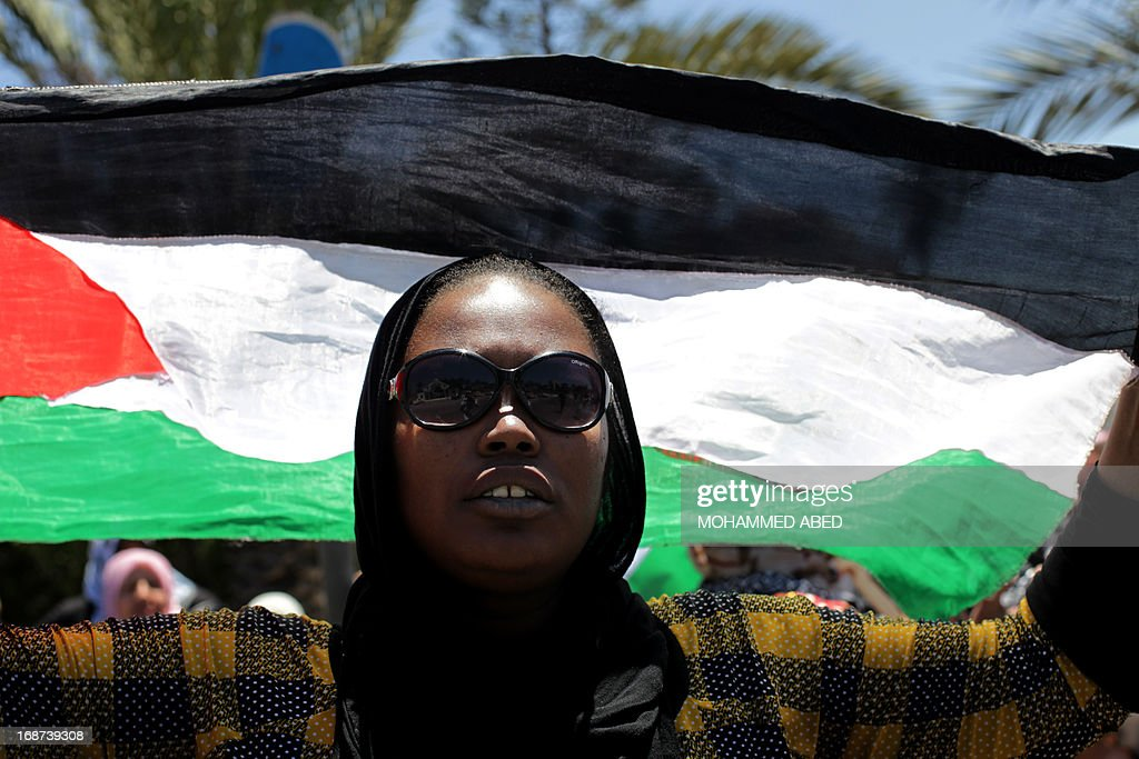 A Palestinian woman holds up her national flag during a Nakba (catastrophe) rally in Gaza City, on May 14, 2013. Palestinians mark Nakba, or catastrophe in Arabic, which commemorates the exodus of hundreds of thousands of Palestinians after the establishment of Israel state in 1948.