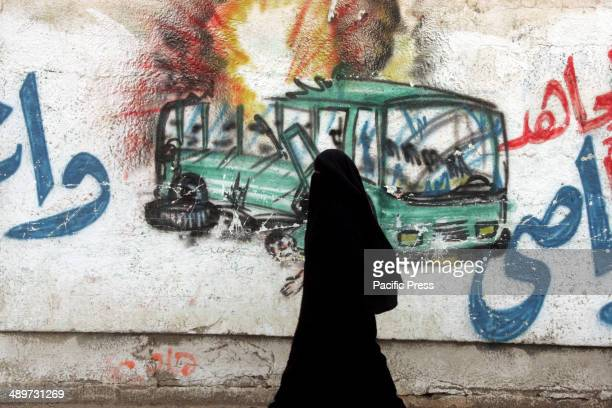 Palestinian woman in Rafah in the southern Gaza Strip walks next to a wall drawing/mural of a militant carrying out a rocket attack on a bus Nakba or...