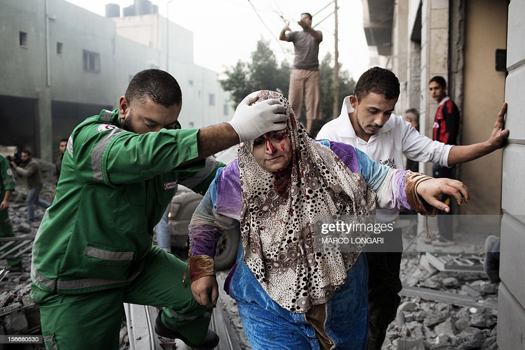 A Palestinian woman is helped by a paramedic out of her building, damaged during an Israeli air raid on a nearby sporting centre in Gaza City November 19, 2012. Israeli air strikes on Sunday killed 31 Palestinians in the bloodiest day so far of its air campaign on the Gaza Strip, as diplomatic efforts to broker a truce intensified. AFP PHOTO/MARCO LONGARI