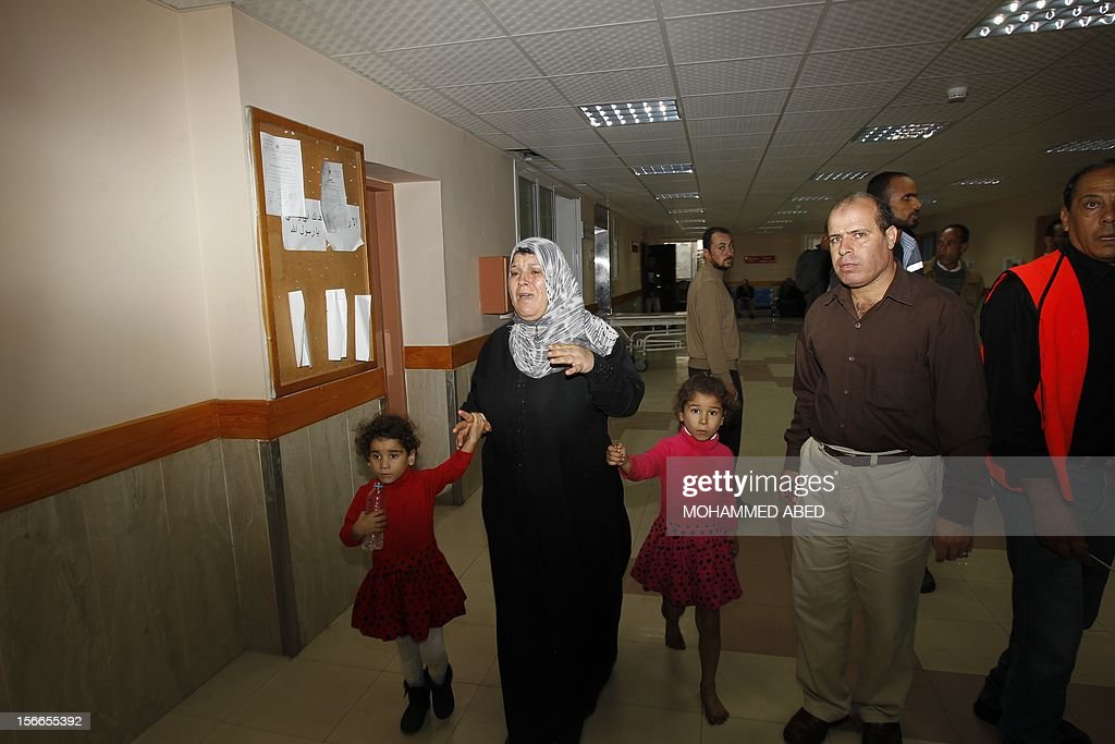 A Palestinian woman leads her two daughters as she grieves at the hospital in Gaza City on November 18, 2012, after seven members of the same family, including four children, were among nine people killed when an Israeli missile struck a family home in Gaza City, the health ministry said.