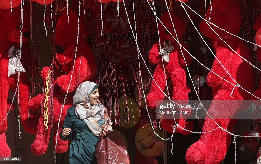 A Palestinian woman leaves a shop displaying red teddy bears on Valentine's Day on February 14, 2016 in Gaza City. / AFP / MAHMUD HAMS