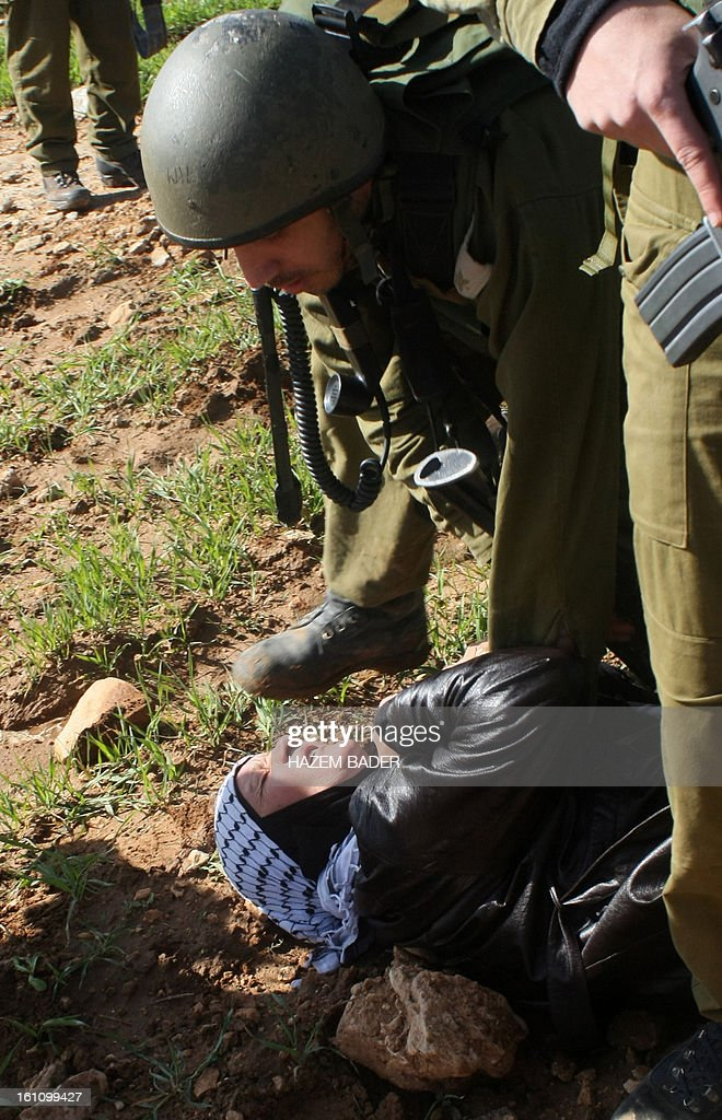 A Palestinian woman lies on the ground being arrested by an Israeli soldier as Palestinian activists tried to set up a new encampment to protest against settlement building in the Yatta, south of the West Bank city of Hebron on February 9, 2013. Soldiers dismantled tents that were being erected in two different areas near the town of Yatta, and forced activists to leave, the Palestinian witnesses said. BADER