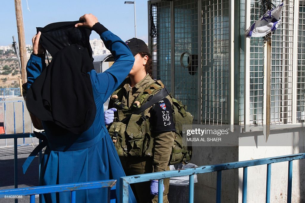 A Palestinian woman lifts her face-veil as she is checked by an Israeli border guard at an Israeli checkpoint between the West Bank town of Bethlehem and Jerusalem, in order to cross to Jerusalem's Al-Aqsa Mosque compound on the forth and last Friday of the Muslim holy month of Ramadan on July 1 , 2016. Israeli authorities announced on June 28 they were closing Jerusalem's flashpoint Al-Aqsa mosque compound to non-Muslim visitors until the end of the Muslim holy month of Ramadan after a series of clashes between worshippers and Israeli police. Clashes have been taking place every morning since the beginning of the week over Jewish visits to the site, with youths throwing stones and security forces firing tear gas and sponge-tipped bullets. / AFP / MUSA