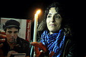 Palestinian woman lights a candle in a commemoration of the 3rd anniversary of Italian activist Vittoro Arrigoni's death at the Gaza port in Gaza...
