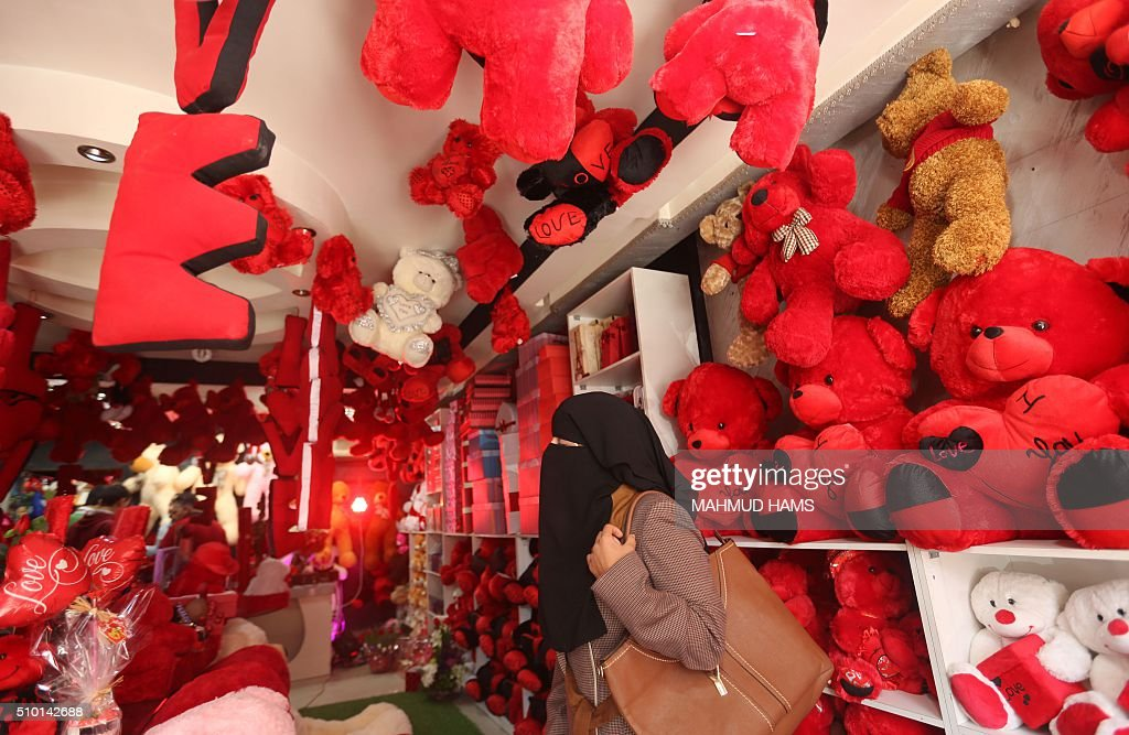 A Palestinian woman looks at red teddy bears displayed at a gift shop on Valentine's Day on February 14, 2016 in Gaza City. / AFP / MAHMUD HAMS