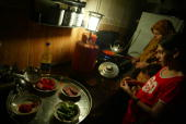 Palestinian woman makes dinner with her daughter by candle light during a power outage August 21 2007 in Gaza City Gaza