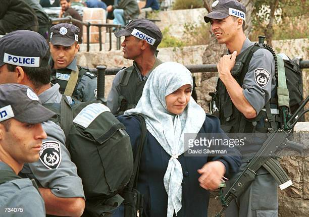 Palestinian woman on her way to Moslem Friday prayers at alAqsa mosque walks past Israeli riot police who block the entrance to Jerusalem's Old City...