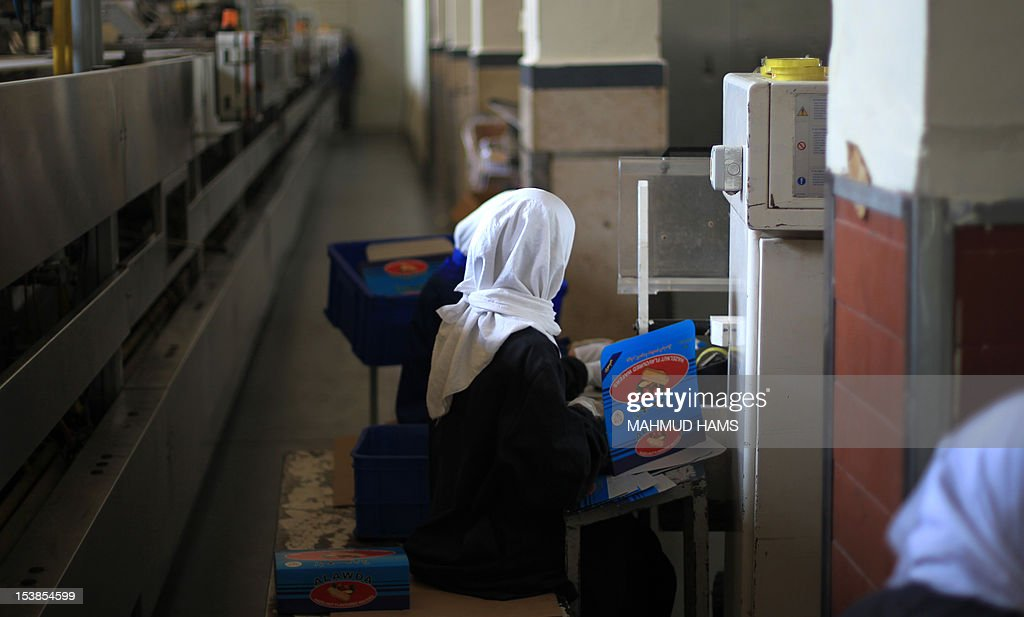 A Palestinian woman packs boxes of biscuits at the al-Awda factory in Deir al-Balah, in the central Gaza strip, on October 10, 2012. The World Food Program (WFP) will export the biscuits to United Nation run schools in the Israeli occupied Palestinian West Bank, the first time since 2006 when the Gaza Strip was put under an Israeli blockade.