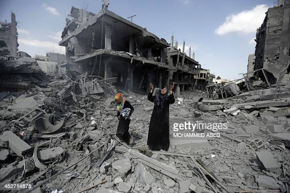 A Palestinian woman pauses amid destroyed buildings in the northern district of Beit Hanun in the Gaza Strip during an humanitarian truce on July 26...