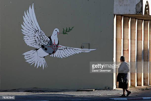 Palestinian woman pauses to look at a wall painting by elusive British graffiti artist Banksy December 5 2007 on a shop wall in the biblical city of...
