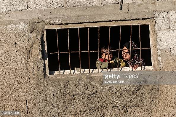 Palestinian woman peers through the window of her house in an impoverished area in the southern Gaza Strip town of Khan Yunis on February 19 2017 /...