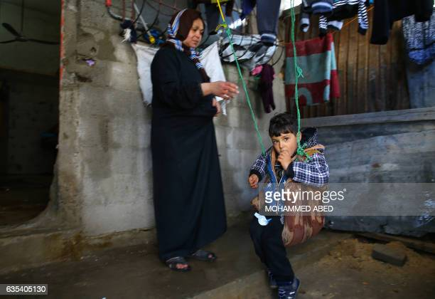 A Palestinian woman pushes her son sitting on a makeshift swing at their empoverished house near the ruins of a building destroyed during the 50day...