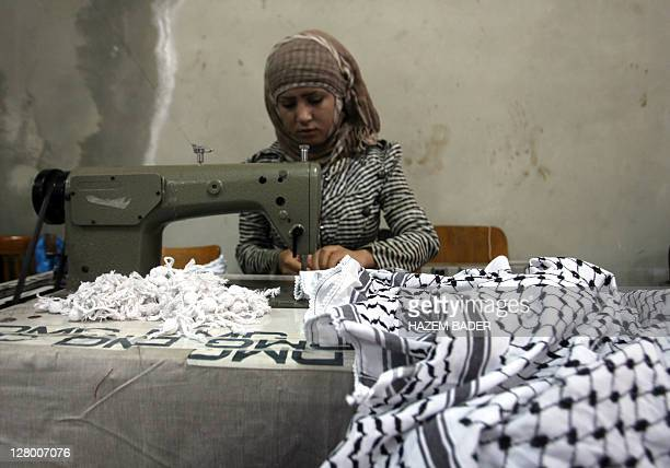 Palestinian woman puts the final touches to the iconic blackandwhite keffiyeh scarves worn by the late Palestinian leader Yasser Arafat at a small...