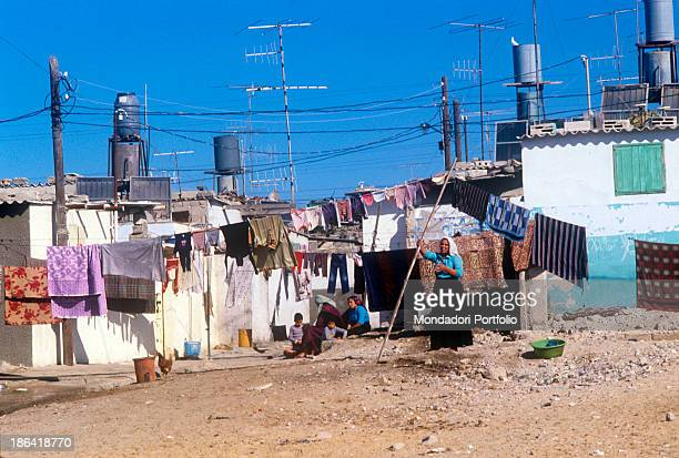 Palestinian woman raising a pole to hang out the washing in a refugee camp Since the SixDay War in 1967 Jewish Israeli people occupied the Gaza Strip...