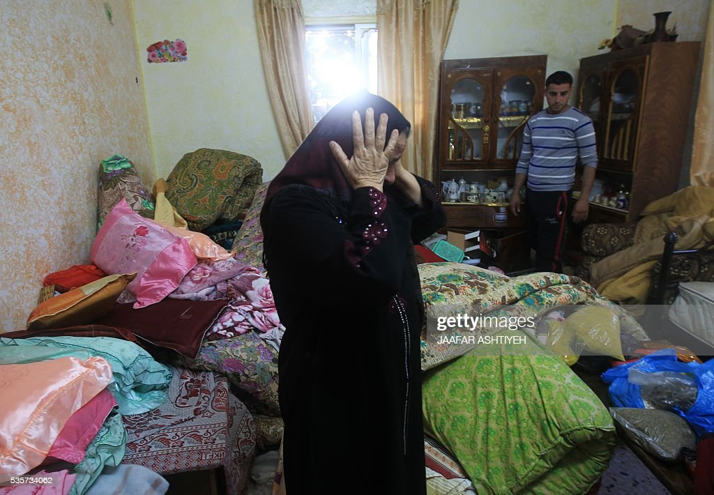 A Palestinian woman reacts as she stands in an overturned room after Israeli troops searched the house during an operation to arrest wanted Palestinians in the northern West Bank village of Deir al-Hatab, east of Nablus, early on May 30, 2016. / AFP / JAAFAR